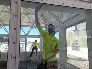 Greg and Tristen Spencer applying window tint to SAM at Biosphere 2